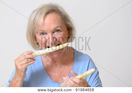 Happy Healthy Senior Lady With A White Asparagus