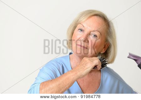 Senior Woman Blow Drying Her Blond Hair