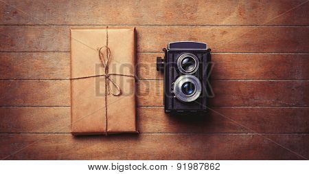Vintage Camera And Package On Wooden Table.