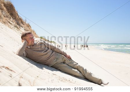 man 45 years old relaxing on beach, lying on sand dune