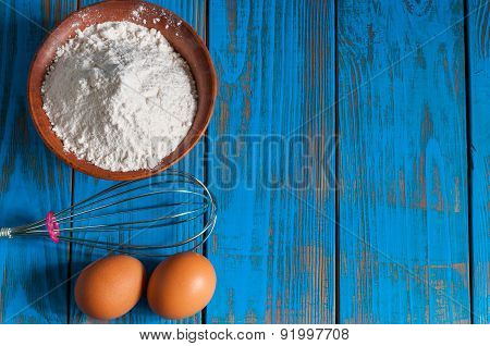 Baking cake in rural kitchen - dough recipe ingredients eggs, flour and whisk on vintage wood table