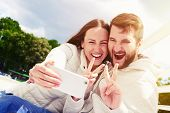 picture of peace-sign  - outdoors photo of joyous couple showing peace sign and taking selfie by mobilephone - JPG