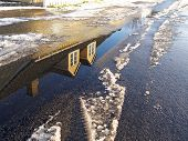 image of icy road  - Winter concept background image house reflected in water pond and snow on the road - JPG