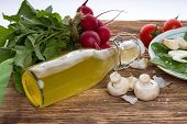 stock photo of champignons  - Horizontal photo of two champignons next to bottle with homemade lemonade and various vegetable around as radishes tomatoes and garlic - JPG