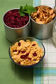 stock photo of milk glass  - Vertical photo with upper view on glass bowl full of cornflakes with cranberries in - JPG
