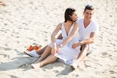 foto of couple sitting beach  - Young couple sitting on a sand beach - JPG