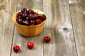 foto of black-cherry  - Close up image of freshly picked whole black cherries in bowl on rustic wooden table - JPG