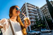 foto of walking away  - Young woman walking on the street with take away coffee  in the transparent cup in the city - JPG