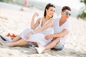 picture of couple sitting beach  - Young couple sitting on a sand beach - JPG