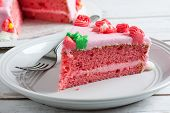 foto of strawberry  - Strawberry layer cake with strawberry frosting and strawberry cream cheese filling on a white plate with a fork and a cake in the background. [[** Note: Shallow depth of field ** Note: Visible grain at 100%, best at smaller sizes - JPG