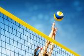 image of balls  - Beachvolley ball player jumps on the net and tries to blocks the ball  - JPG