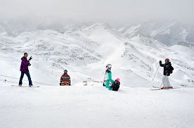 picture of snowboarding  - Happy four sportsmen with snowboard and skis standing on top of mountain - JPG