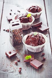 image of chocolate muffin  - Chocolate muffins with chocolate on wooden background - JPG