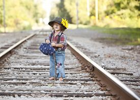 stock photo of hobo  - Adorable toddler on the railroad tracks dressed as a little hobo - JPG