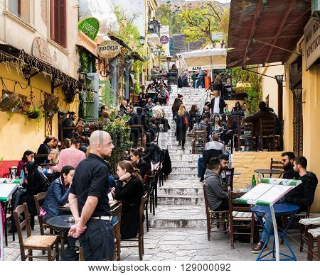 Athens. Greece- March 28. People enjoying their coffee in a popular street of Anafiotika, a small neighborhood in Plaka Athens. It lies in the northerneast side of the Acropolis hill. It was built in the era of Otto of Greece by workers from the Cycladic