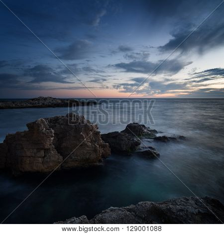 Seascape. Sea coast under blue sky with clouds at sunset