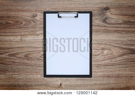Blank white paper sheet A4 on clipboard on wooden background. Blackout frame. Top view