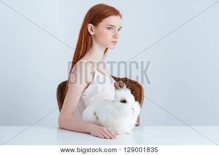 Pensive redhead woman sitting at the table with rabbit and looking away isolated on a white background