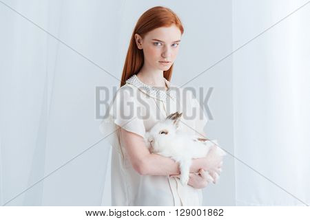 Serious redhead woman holding rabbit isolated on a white background