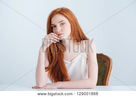 Beautiful redhead woman sitting at the table and looking at camera isolated on a white background