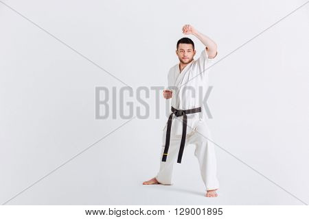 Male fighter in kimono warming up isolated on a white background