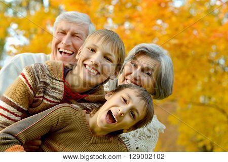 Grandparents and grandchildren together in autumn park