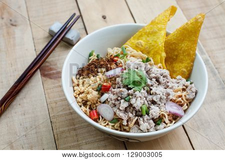 Spicy instant noodle with minced pork on wood background