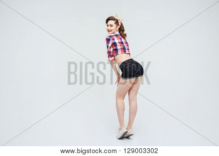 Back view of smiling charming pinup girl in checkered shirt and shorts posing