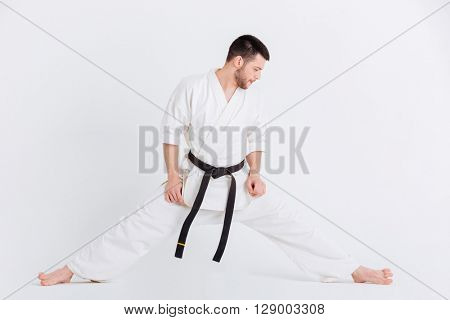 Full length portrait of a man in kimono doing stretching exercises isolated on a white background