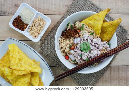 Spicy instant noodle with minced pork on wood background.Topview