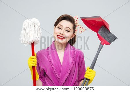 Portrait of cheerful beautiful young housewife in gloves with mop, cleaning brush and dustpan