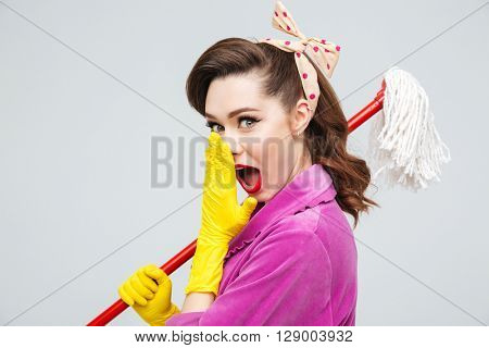 Portrait of wondered beautiful young housewife in yellow rubber gloves holding mop