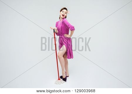 Smiling alluring young housewife standing and posing with mop