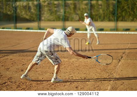 Active senior couple playing tennis outdoors together ** Note: Soft Focus at 100%, best at smaller sizes
