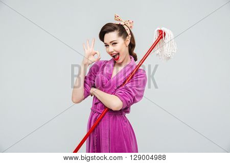 Cheerful charming young housewife holding mop and showing ok sign