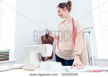 Happy pretty young woman seamstress with laptop working in design studio