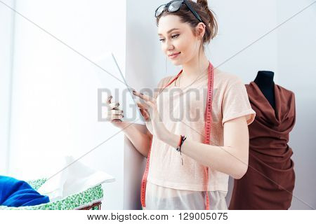 Smiling lovely young woman seamstress standing in design studio and using laptop