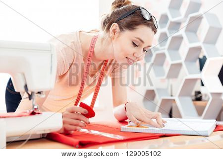 Happy inspired young woman seamstress at work with red fabric