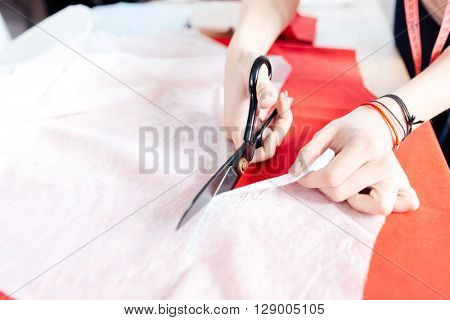 Hands of young woman seamstress with scissors cutting white fabric