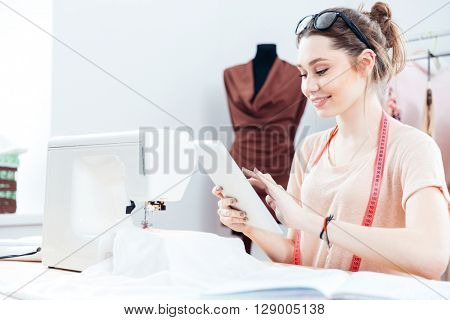 Smiling pretty young woman seamstress sitting and using tablet at work