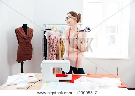Cheerful attractive young woman seamstress with scissors standing and smilig in design studio