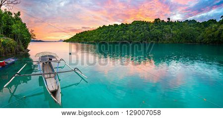 Breathtaking colorful sunset and traditional boat floating on scenic blue lagoon in the Togean (or Togian) Islands Central Sulawesi Indonesia upgrowing travel destination.