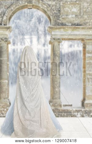 portrait of cloaked woman by castle lake