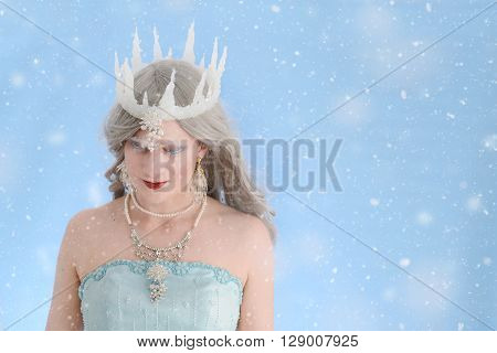 portrait of ice queen with snow and blue background