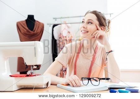 Portrait of happy charming young woman  seamstress thinking and working in studio