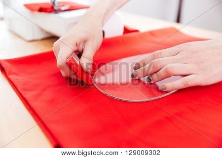 Closeup of hands of young woman seamstress working with pattern and red textile on the table