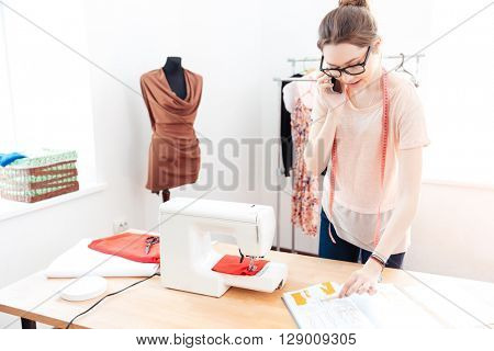 Serious beautiful young woman seamstress working and talking on mobile phone