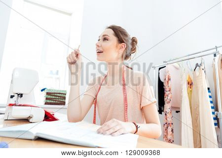 Happy inspired young woman seamstress drawing patterns in notebook and having an idea