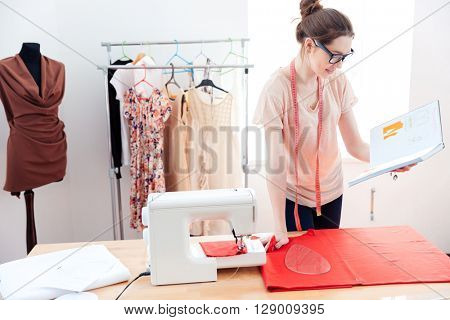 Serious pretty young woman seamstress working with red fabric in studio