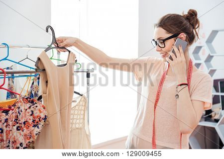 Cheerful beautiful young woman fashion designer choosing dress and talking on mobile phone